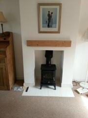 Small-wood-burning-stove-in-neat-inglenook